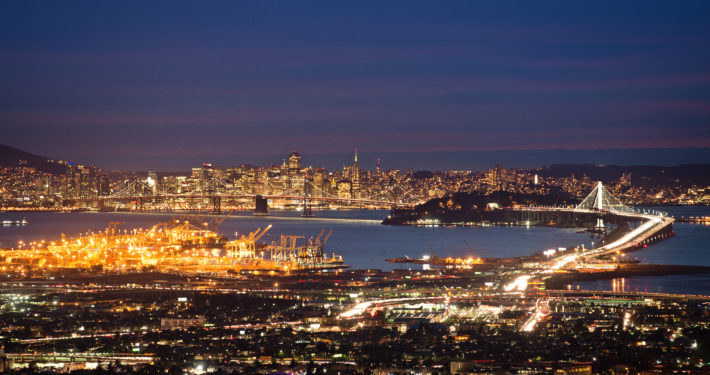 An overall shot of the bay area at night. The lights from the city gleam brightly.